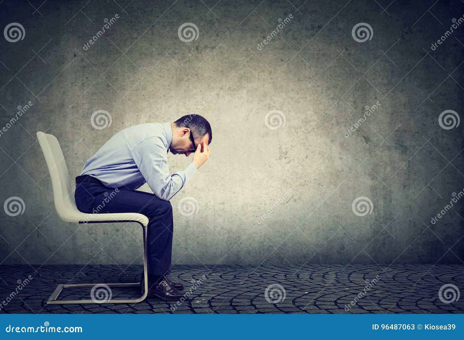 Droevige beklemtoonde zakenmanzitting in een leeg bureau