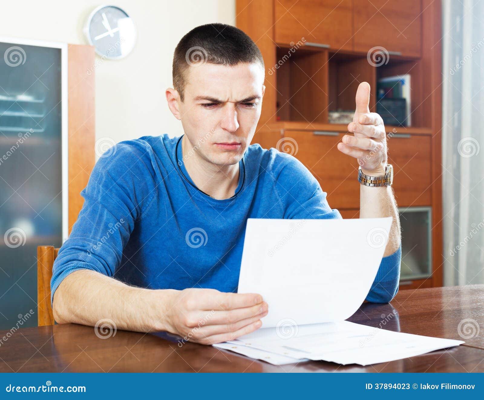 Droevige gefrustreerde mens die stuk van document bekijken