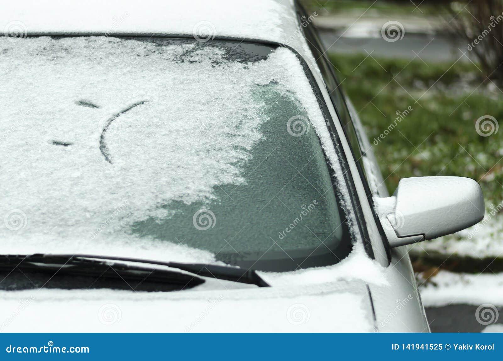 Droevige glimlach op het autoraam in de winter Eerste sneeuw