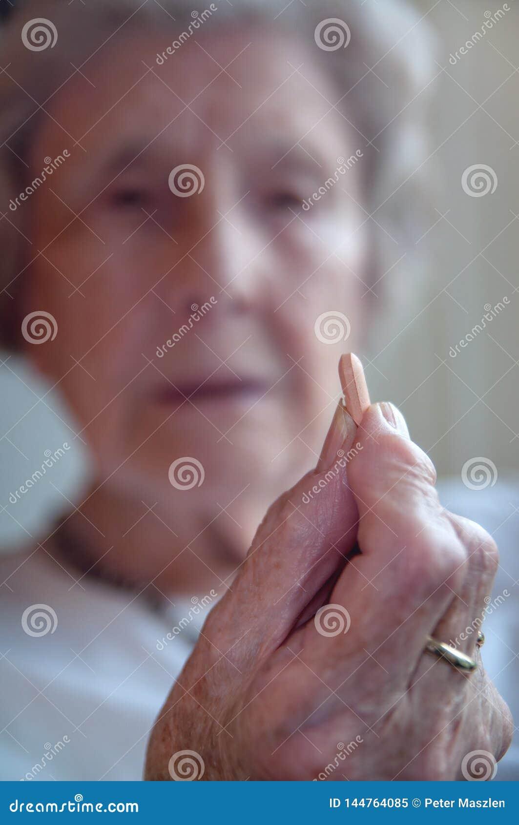 Droevige hogere vrouw die pil nemen