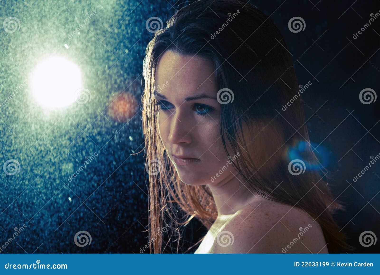 Droevige jonge vrouw in de regen