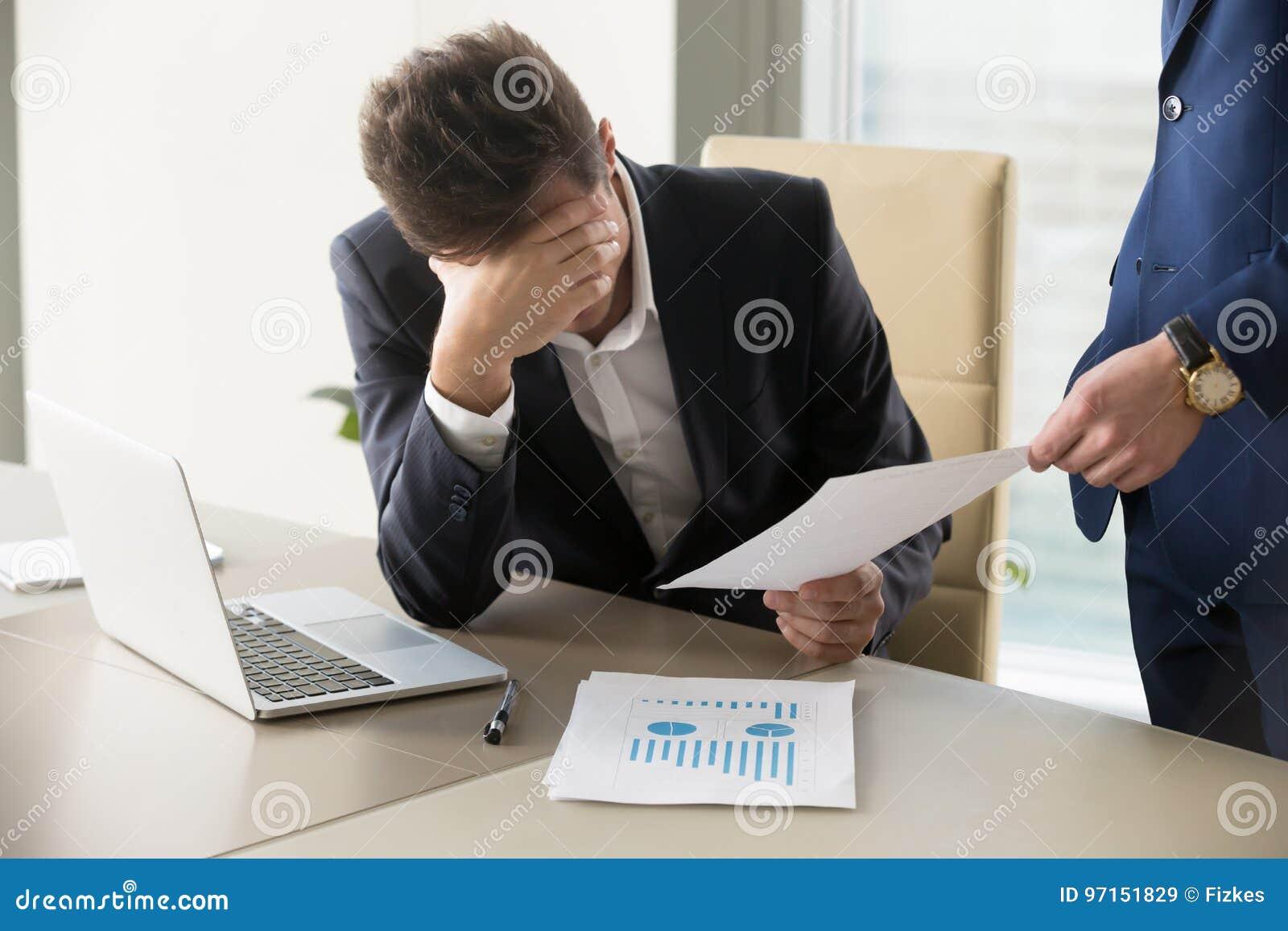 Droevige manager die bericht van ontslag, document met slecht nieuws krijgen