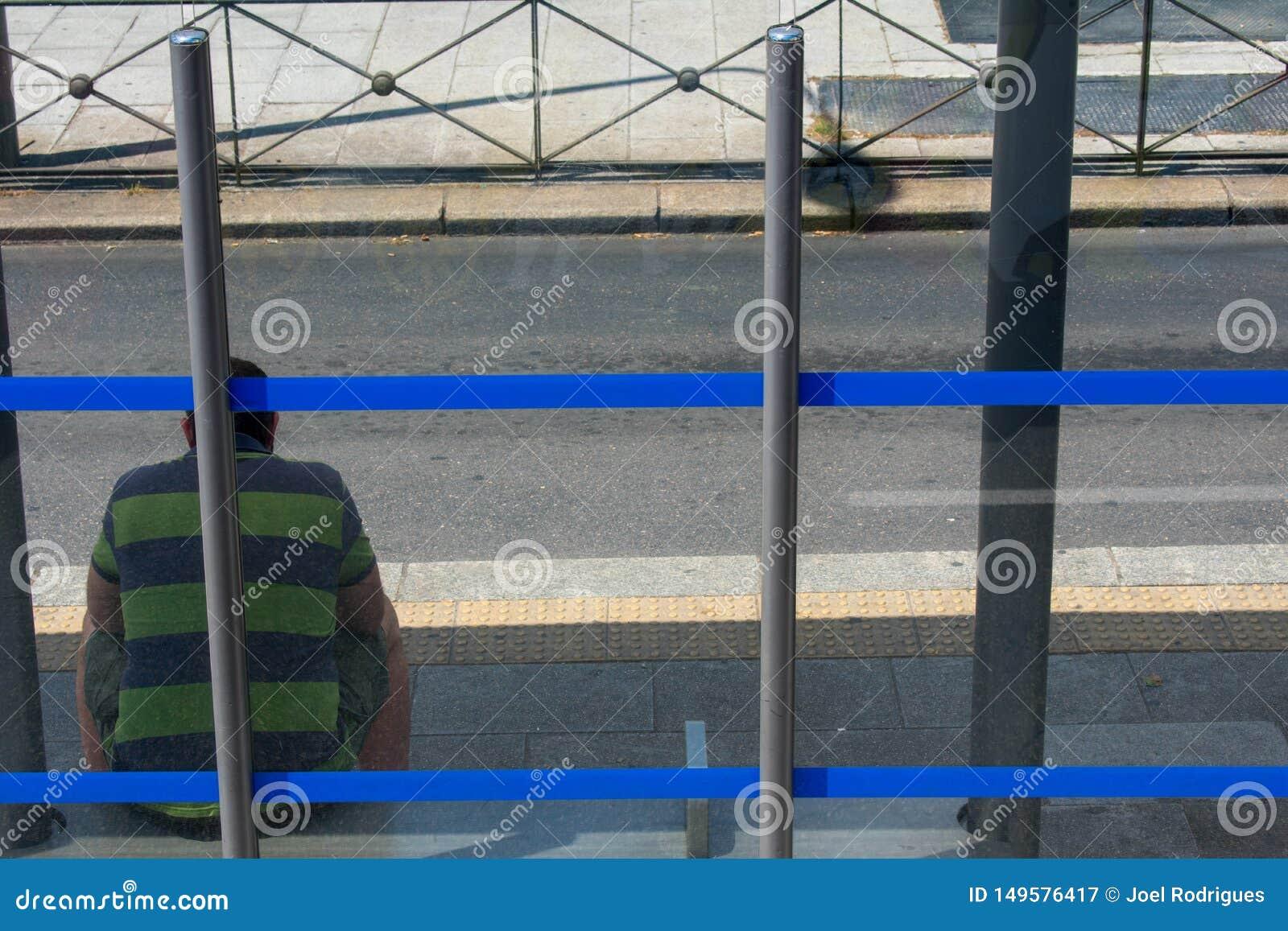 Droevige mensenzitting bij blauwe gestripte bushalte op zonnige dag
