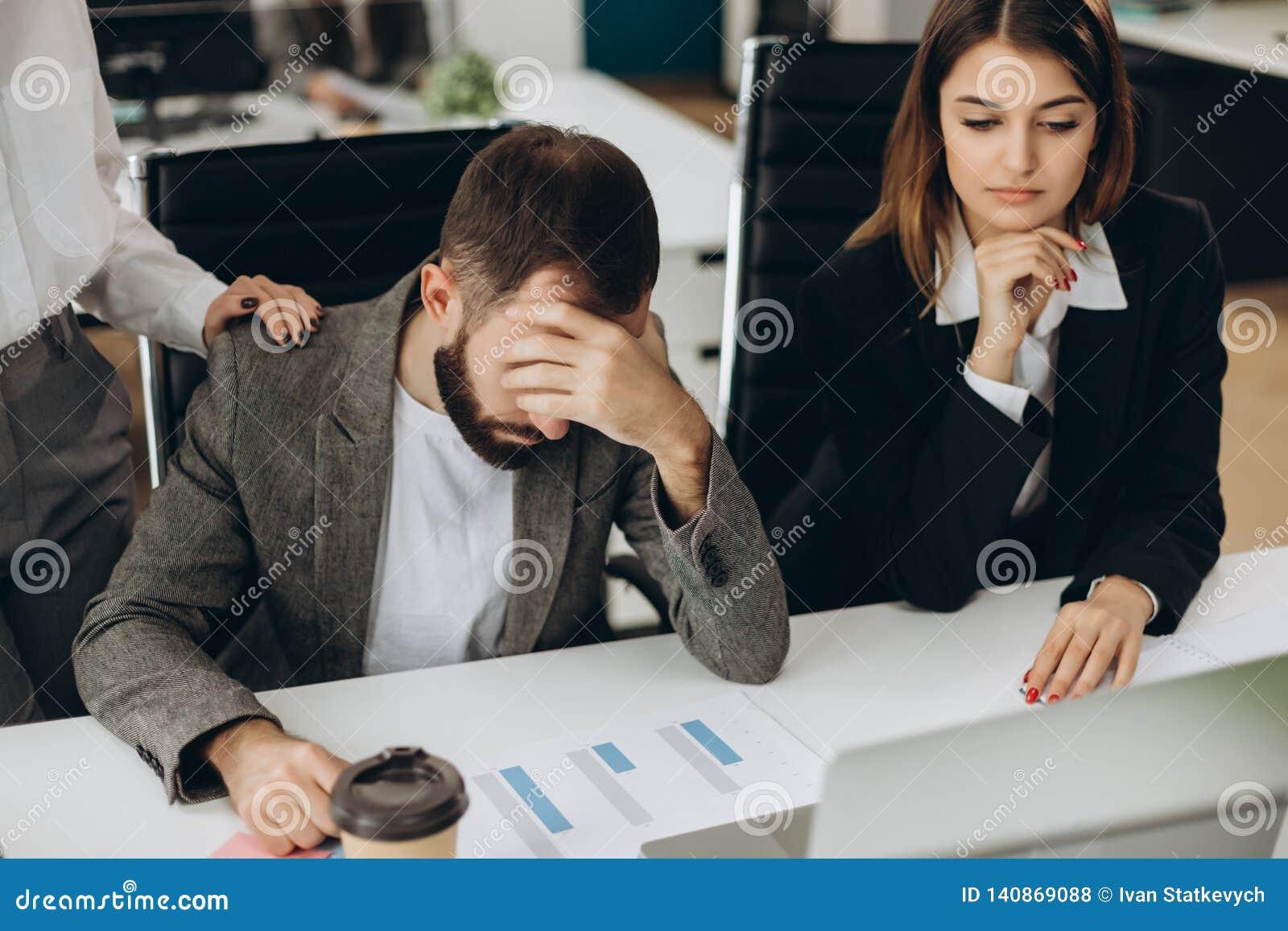 Droevige mensenzitting bij het bureau in bureau die laptop het scherm bekijken die probleem, slecht nieuws hebben Zijaanzicht van