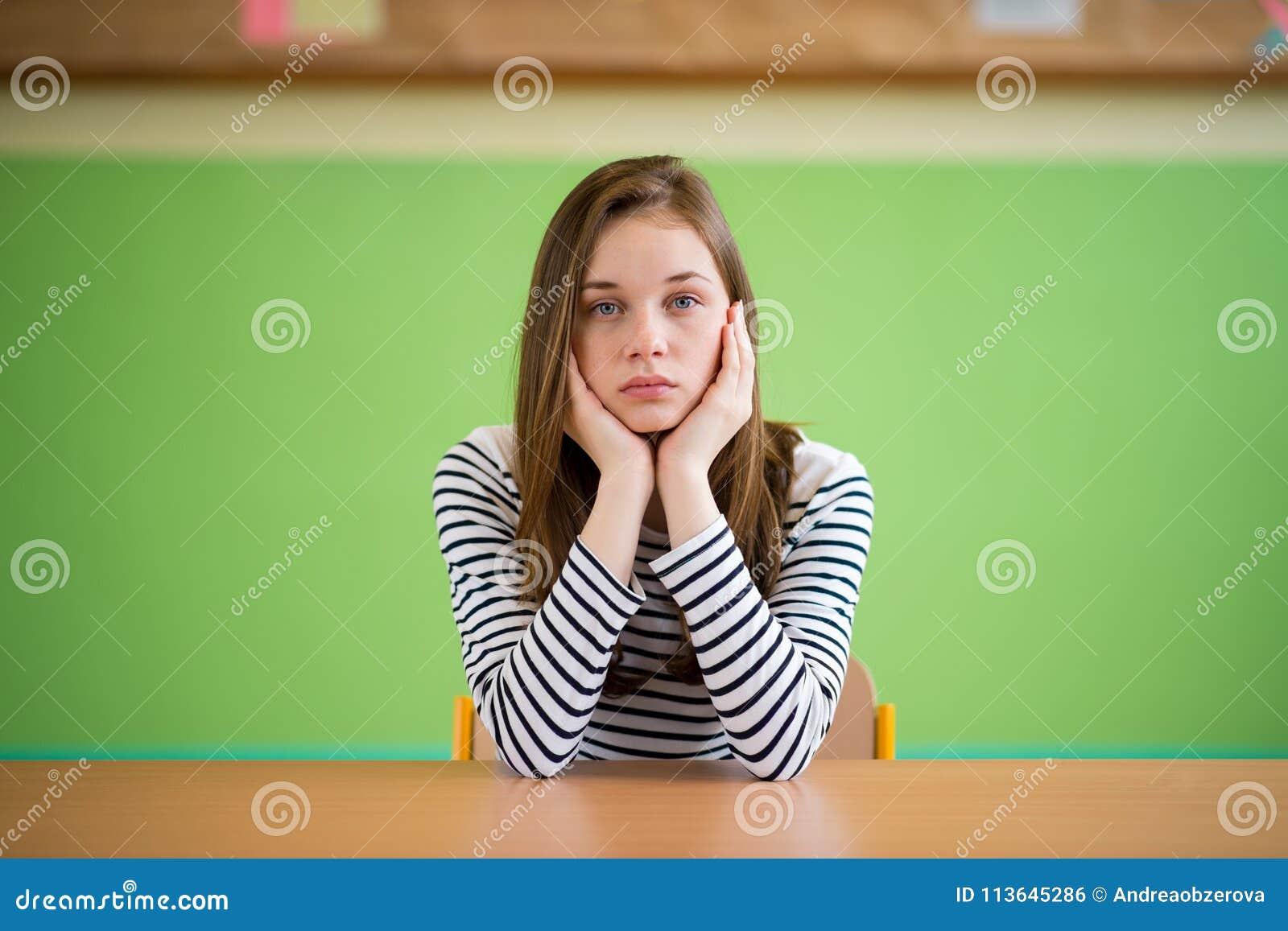 Droevige studentenzitting in klaslokaal met haar hoofd in handen Onderwijs, middelbare school, intimidatie, druk, depressie