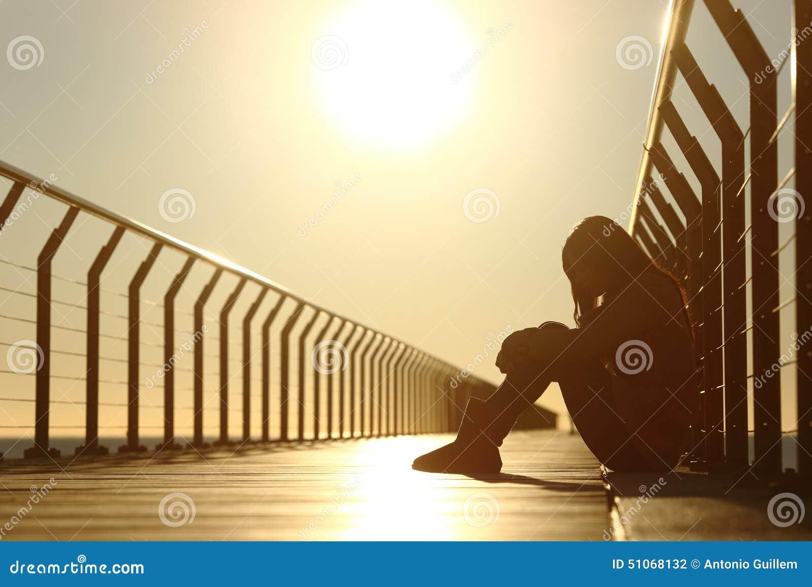 Droevige tienermeisje gedeprimeerde zitting in een brug bij zonsondergang