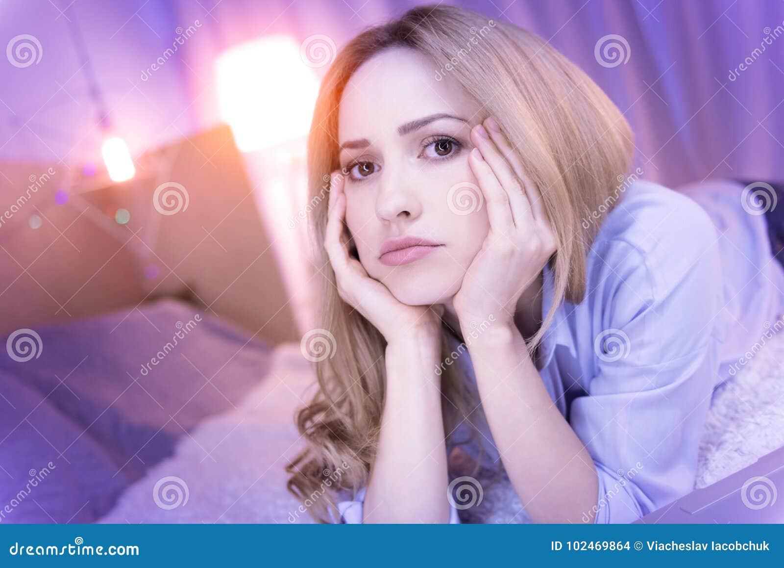 Droevige vrouw die op de bank liggen