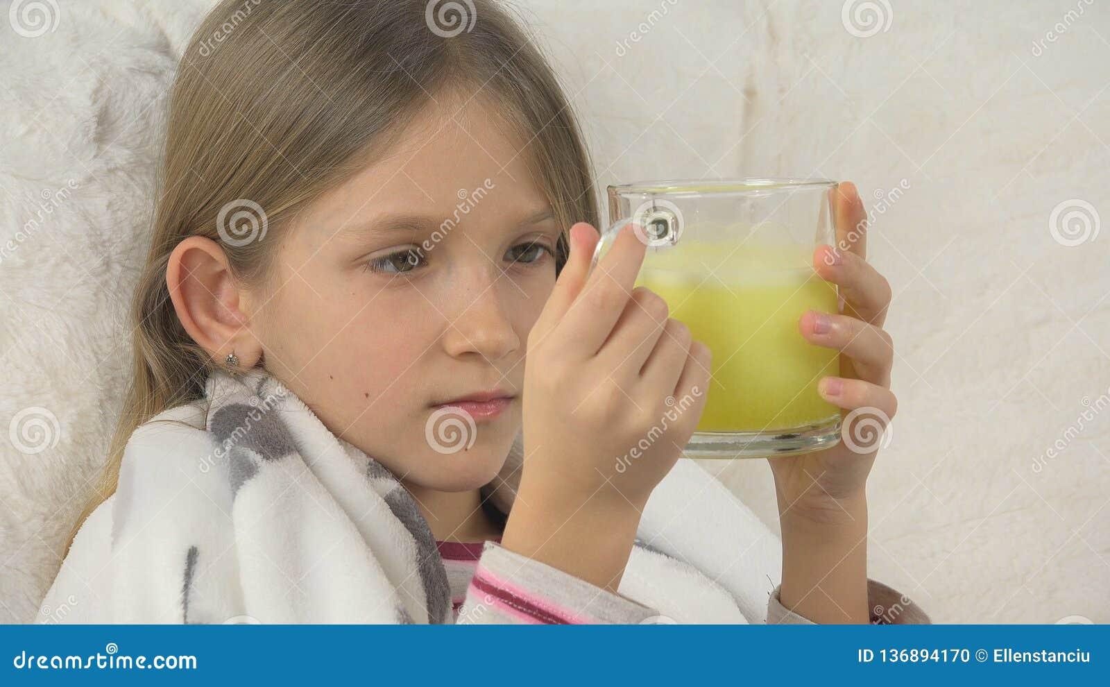 Drogas bebendo da cara doente da criança, menina doente triste, retrato da criança com medicamento, sofá