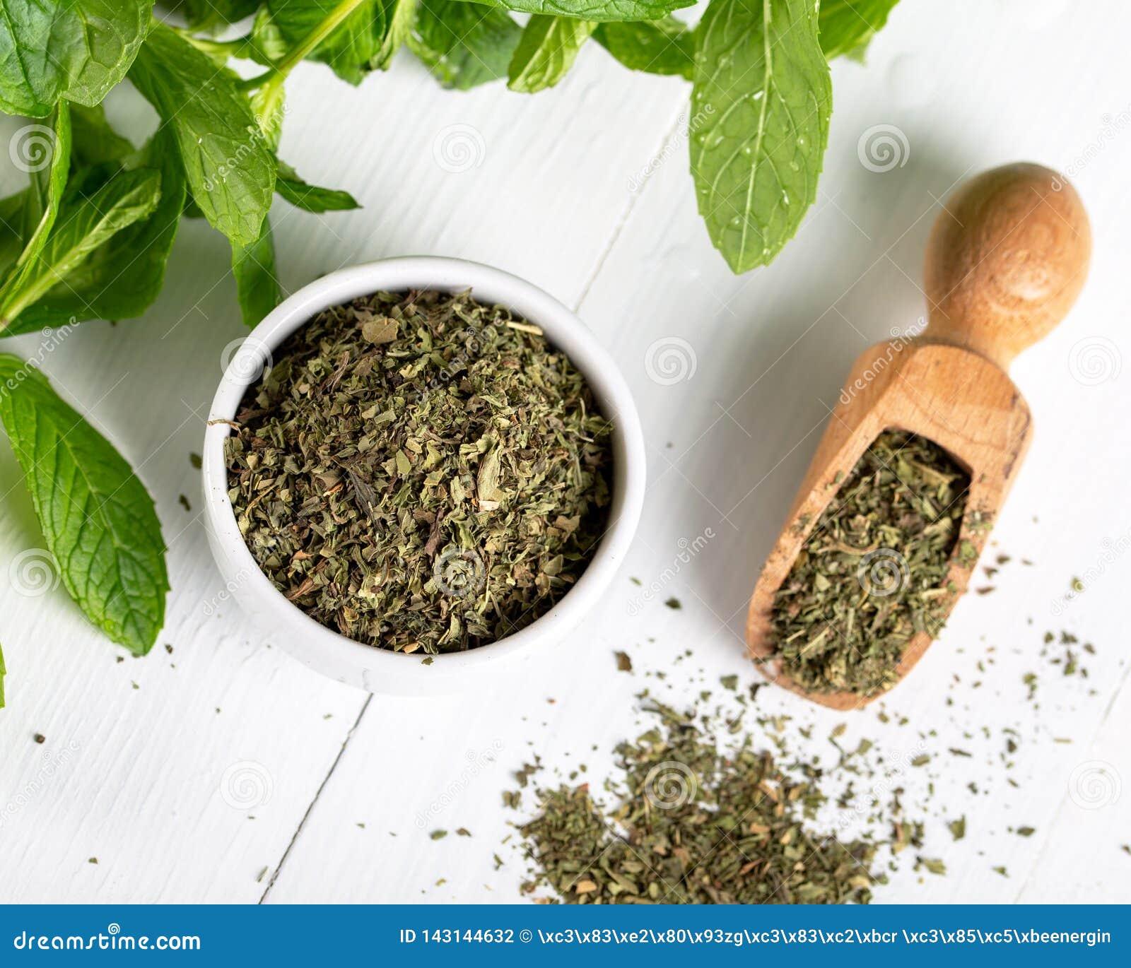 Droge pepermunt in een witte kom en een bos van verse munt, op houten achtergrond