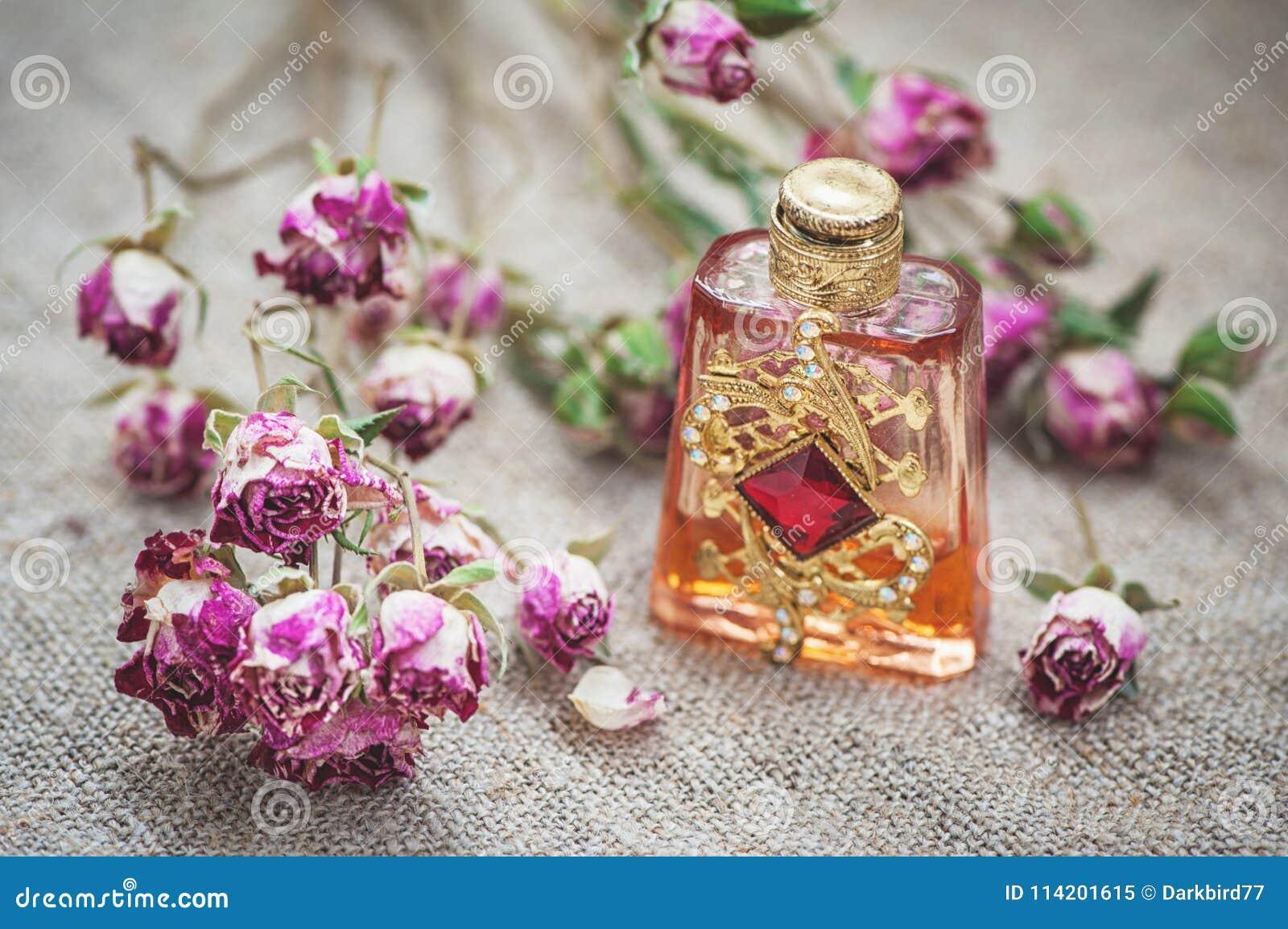 Droge theerozen en uitstekende parfumfles op de jute