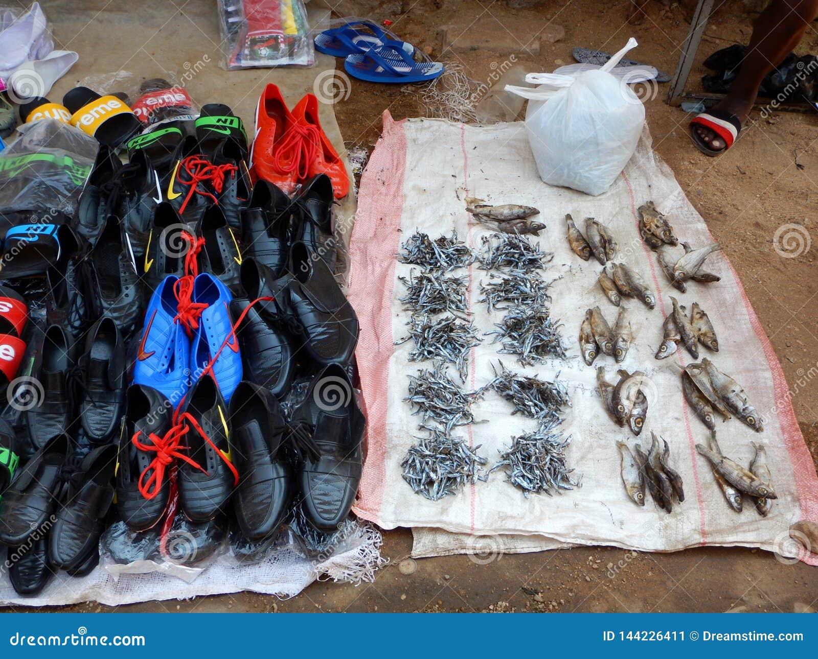 Droge vissen en schoenen voor verkoop in markt in Mozambique