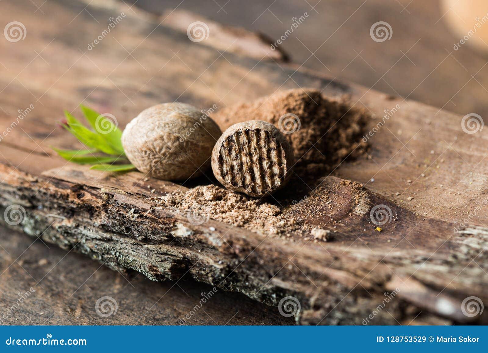 Droge zaden van geurige notemuskaat en geraspte die notemuskaat op witte achtergrond wordt geïsoleerd