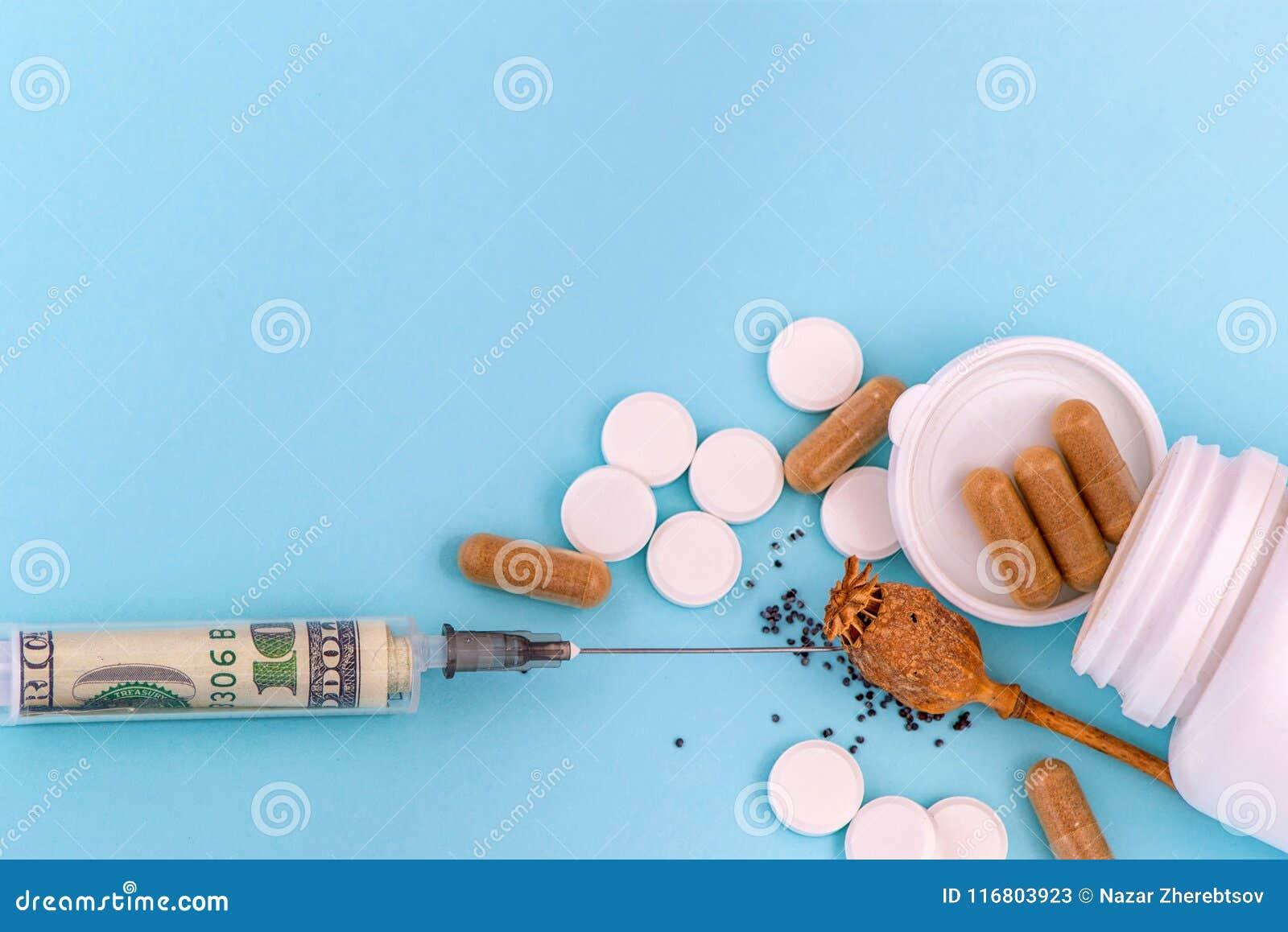 Droghi il papavero da oppio, le pillole e la siringa con un dollaro dentro Su priorità bassa blu
