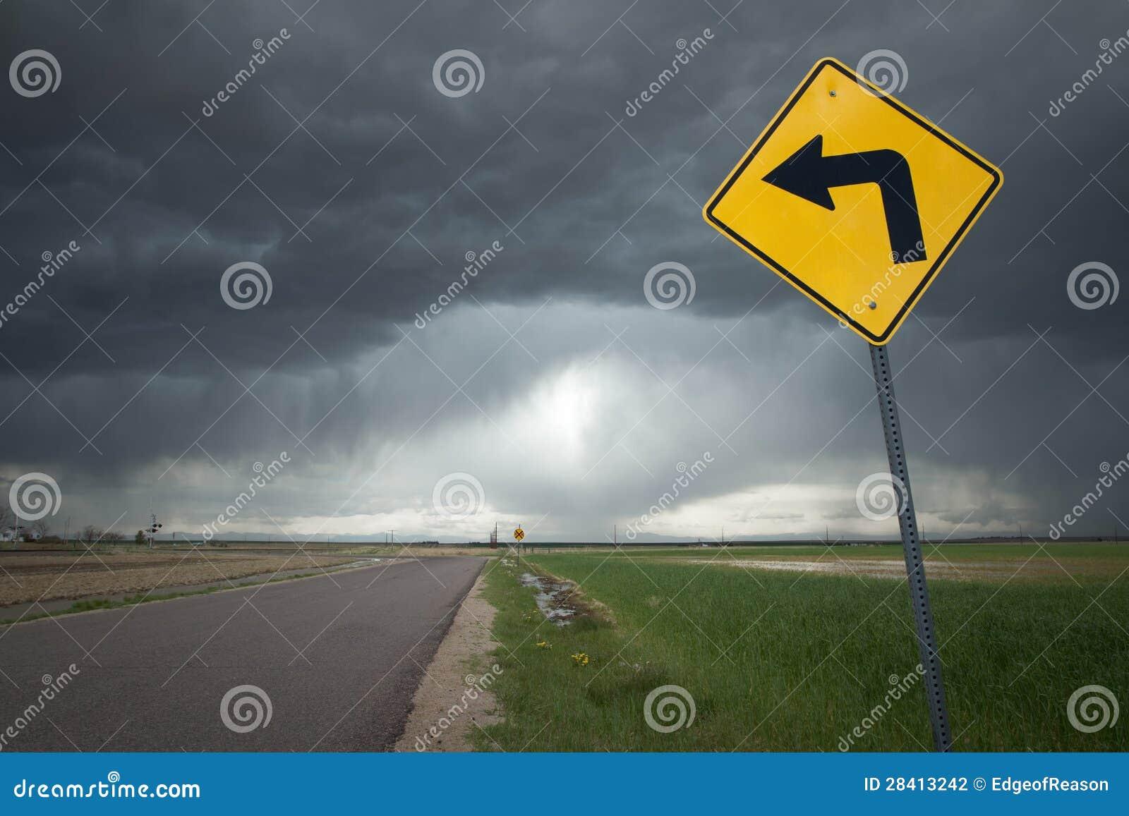 Drogowy znak z skręt w lewo strzała i Złowieszczym burzy tłem