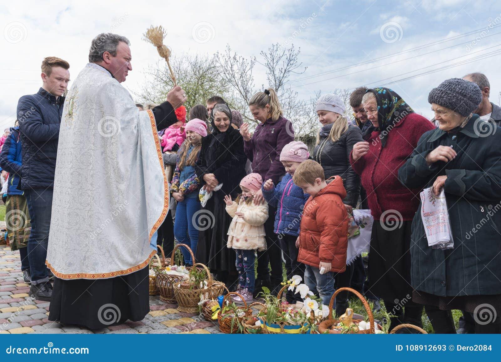 Drohobych, Ucrânia ocidental - 8 de abril de 2017: O padre consagra cestas da Páscoa com água sagrado