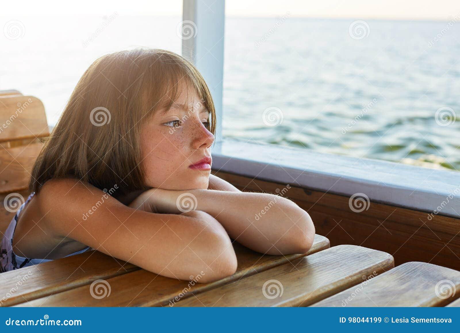 Dromerig weinig vrouwelijk kind die op houten lijst leunen terwijl het hebben van reis op boot, genietend van kalme overzees, die