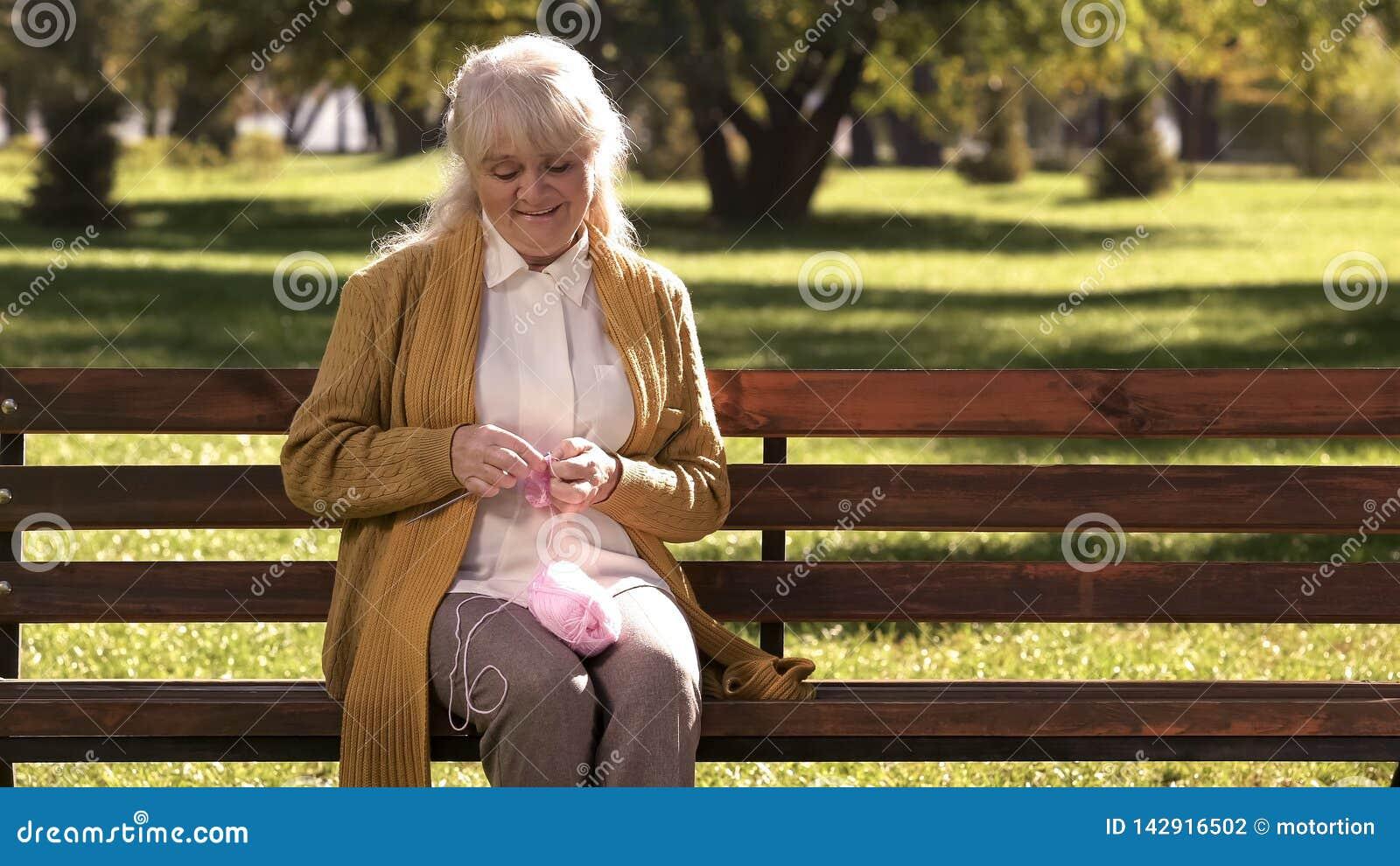 Dromerige oude vrouw die kleine sokken voor haar kleindochter breien, familiegeneraties