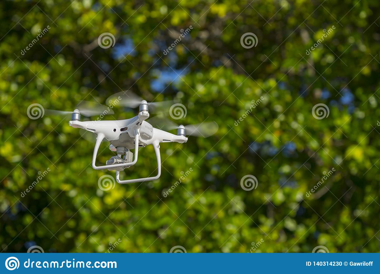 Drone in flight, green trees in the background, selective focus on the drone