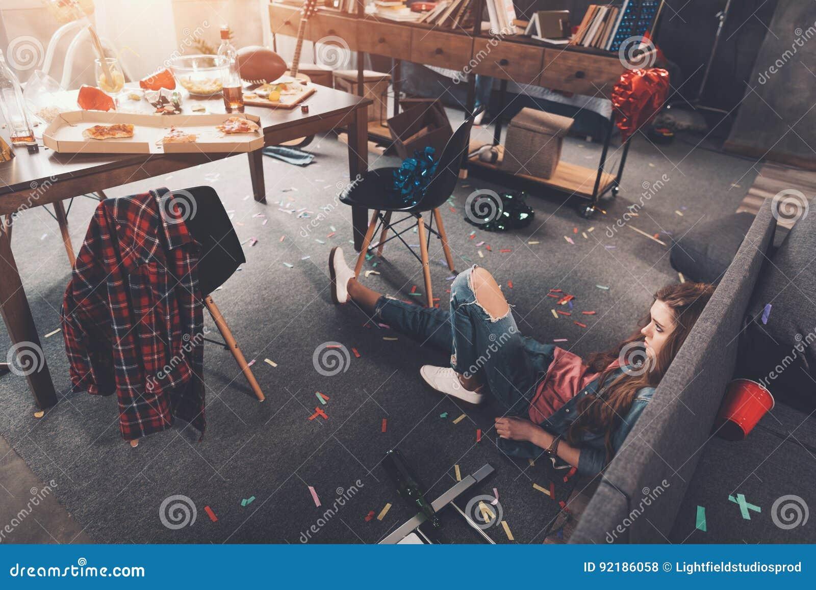 Dronken jonge vrouw die op vloer in slordige ruimte na partij liggen