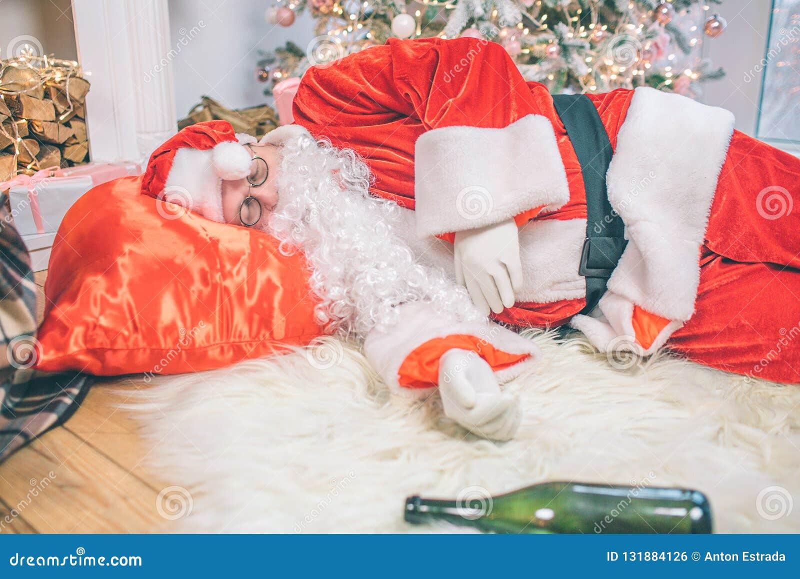 Dronken Santa Claus die bij vloer en het slapen liggen Zijn zak is onder hoofd Fles die op tapijt liggen