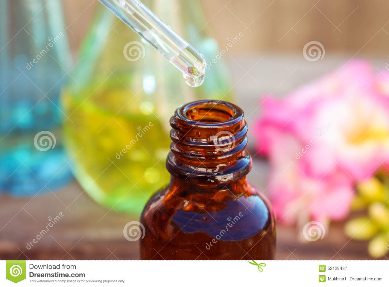 Drop of oil dripping from pipette into bottles of essential oil