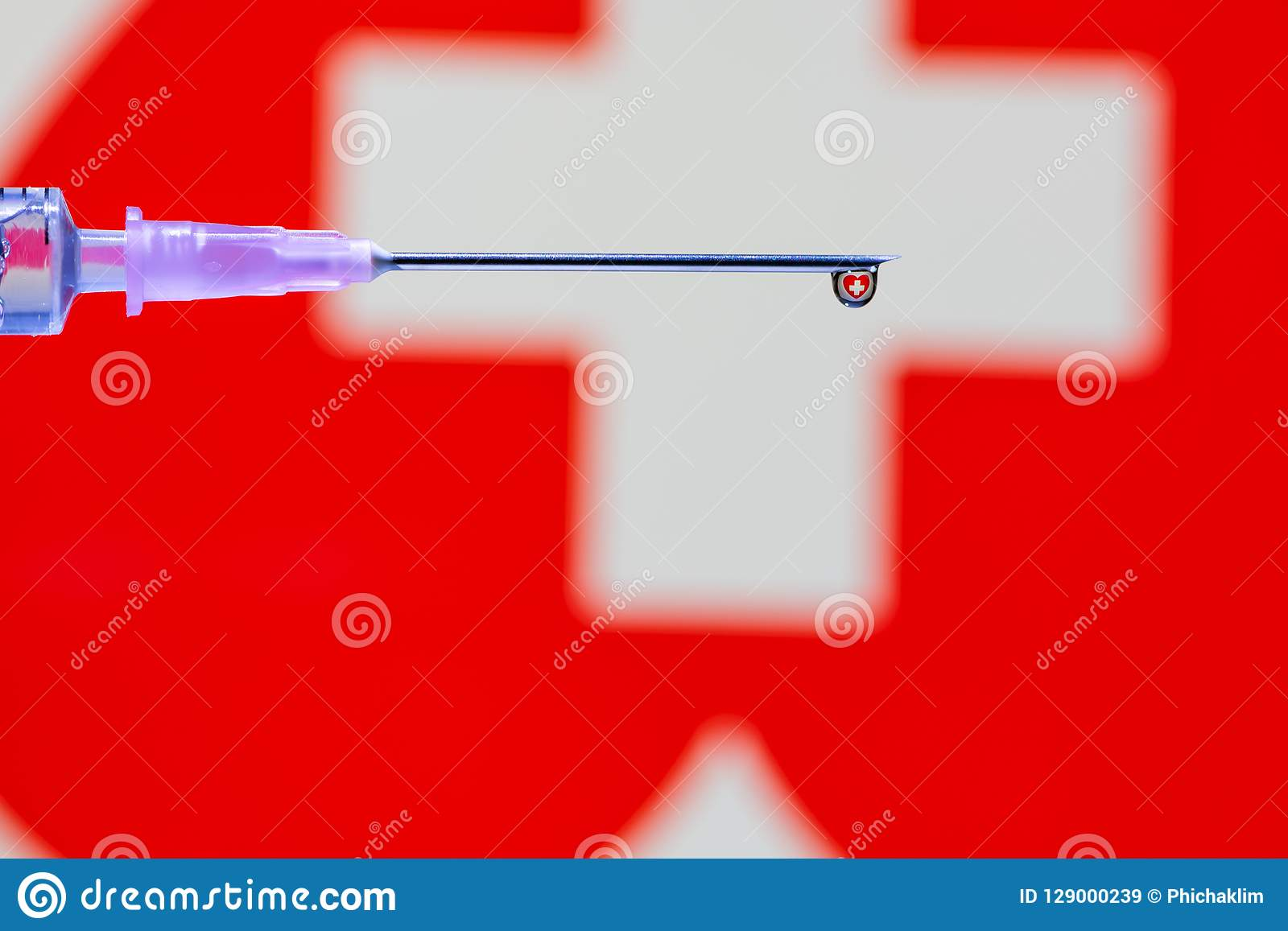A droplet of vaccine at the tip of the needle and syringe