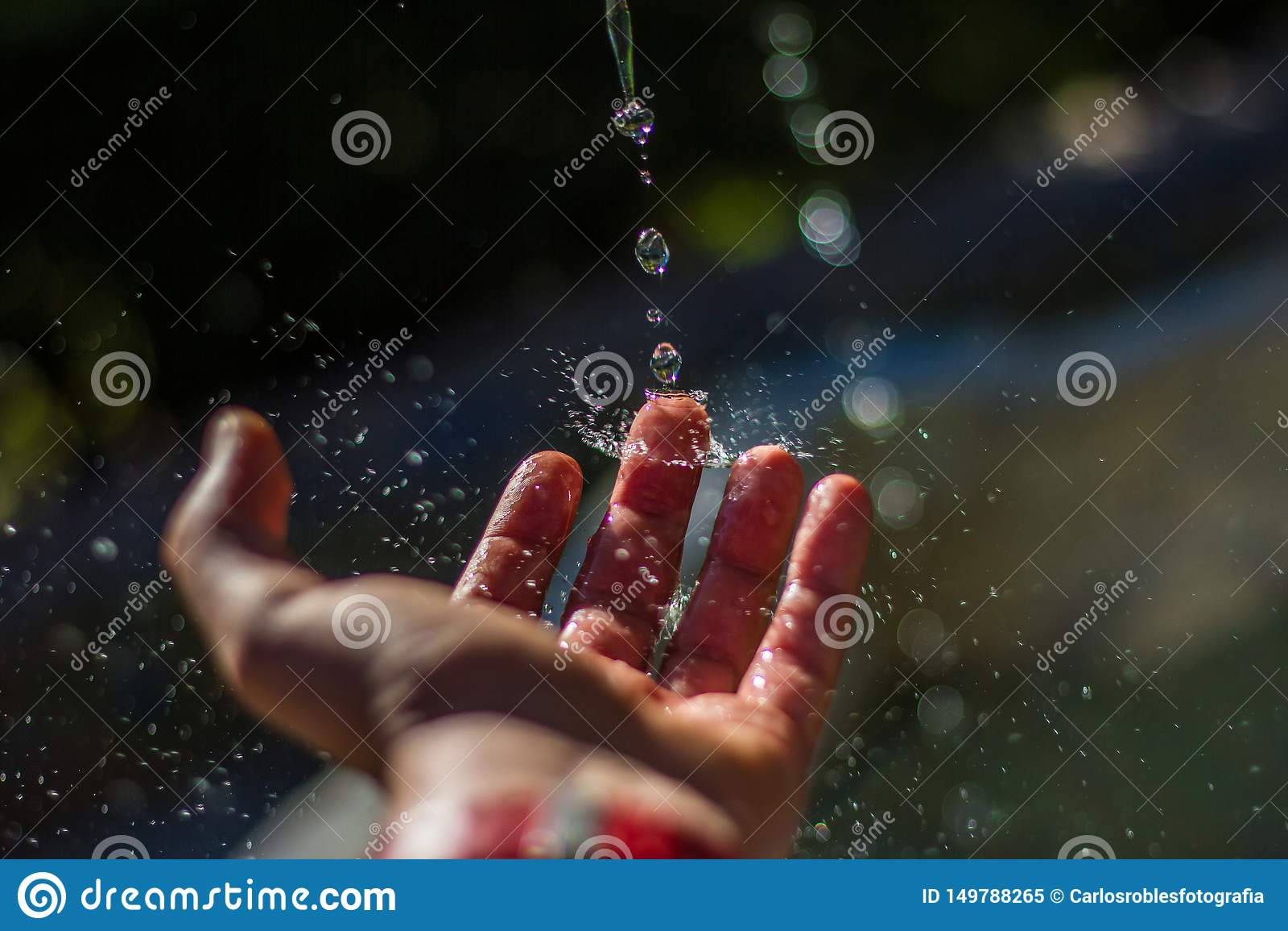 Droppar av vatten som slår fingret