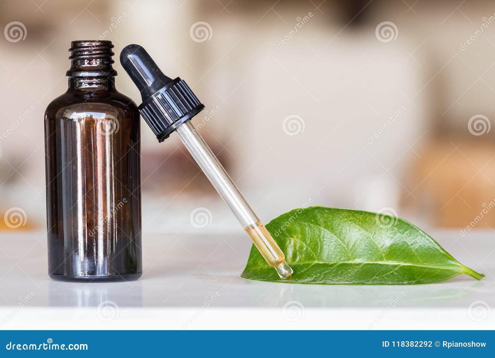 Droppglass med flytande med en flaska och ett grönt blad