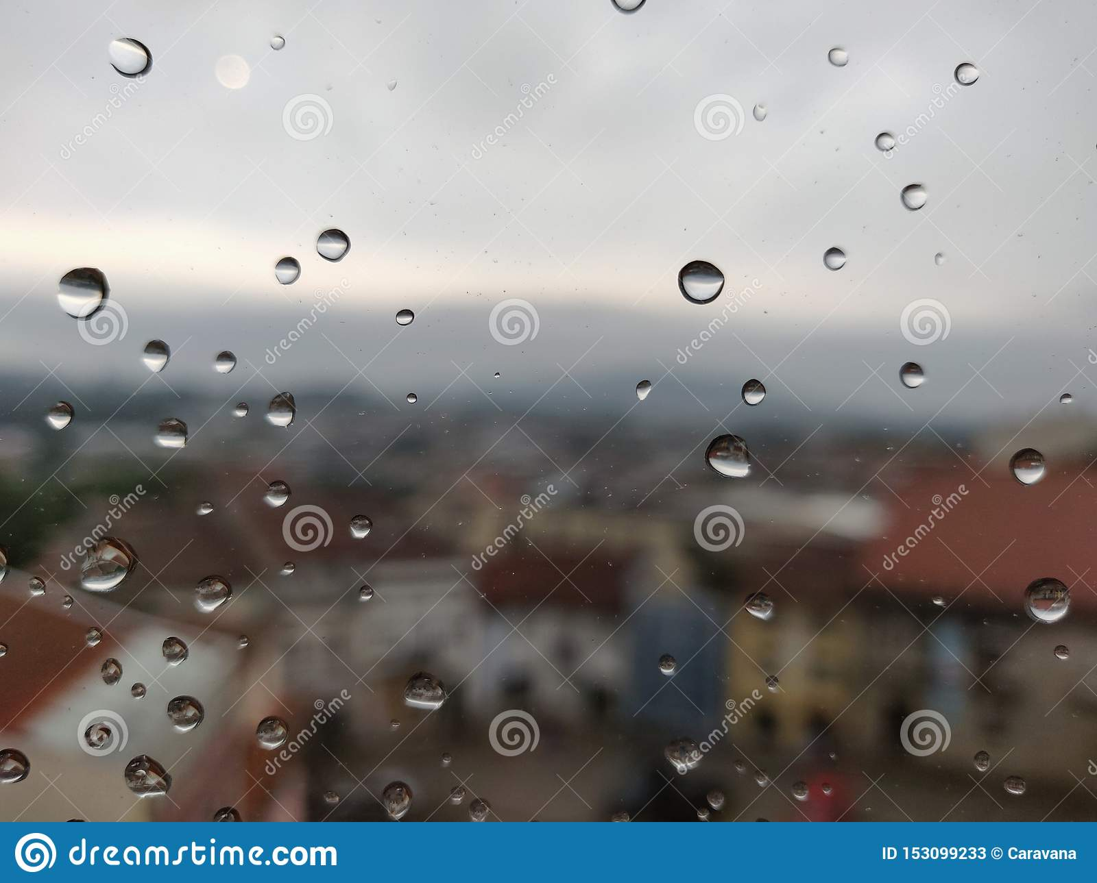 Drops of water in window glass with Barcelos city in background.