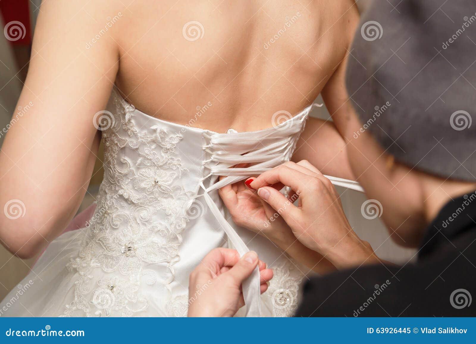 Drużka pomaga panny młodej ubierać faborek