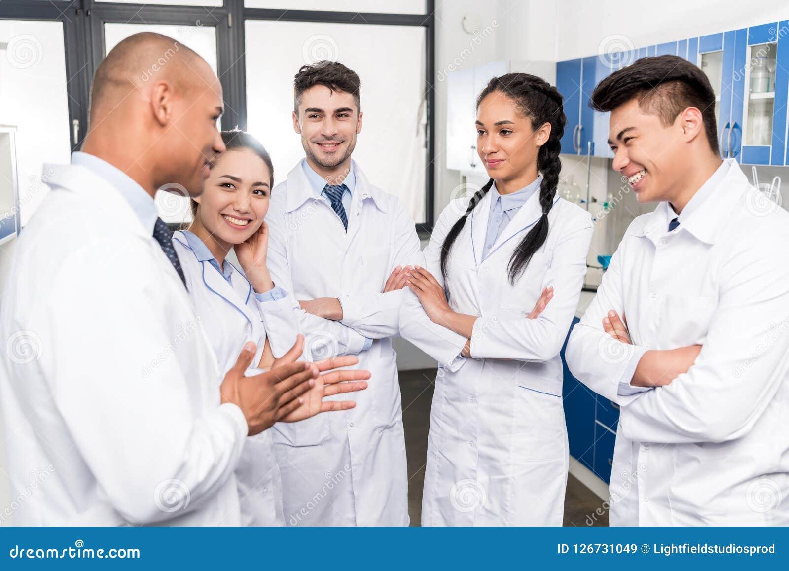 Drużyna młode lekarki dyskutuje pracę w lab żakietach
