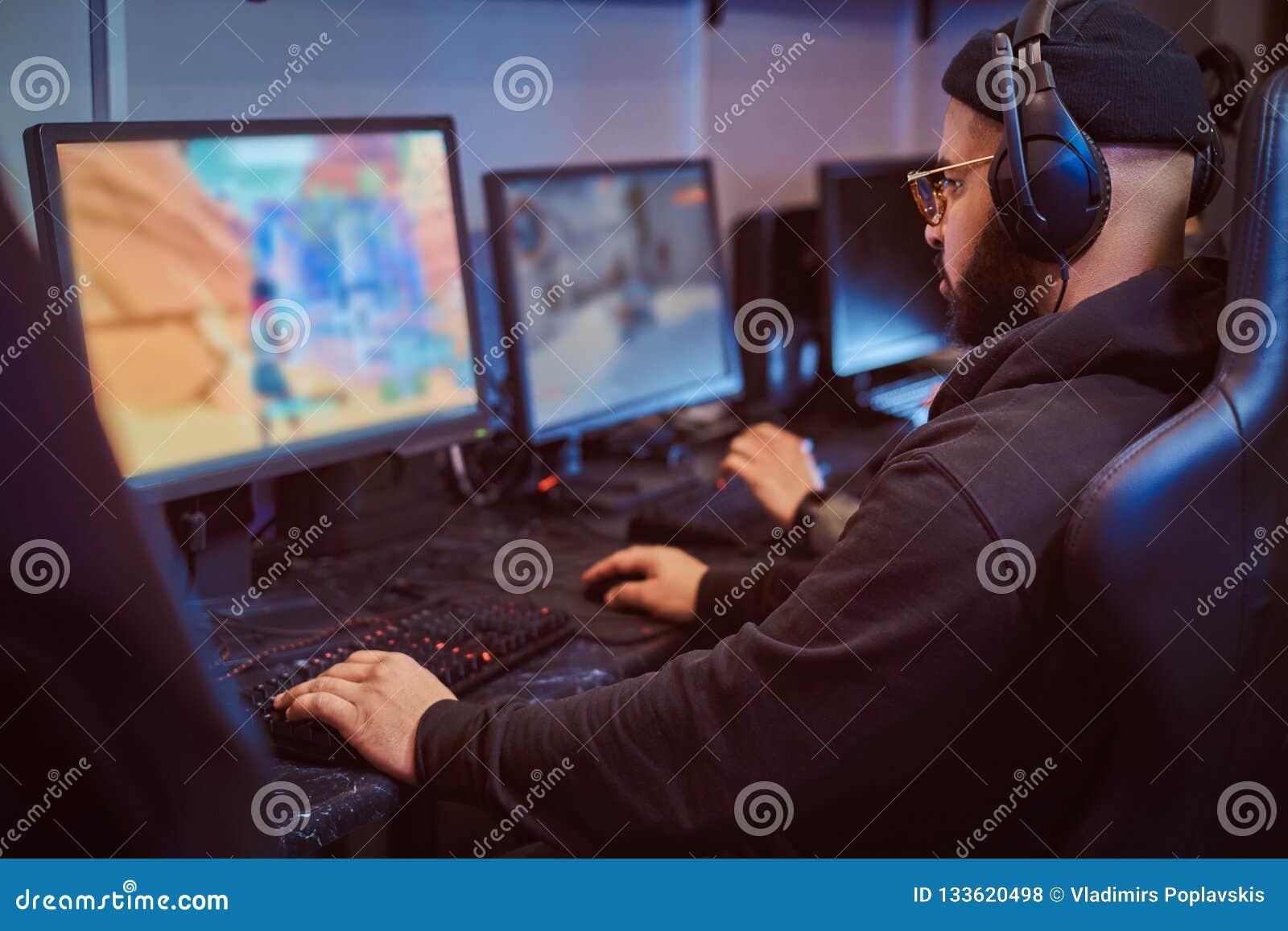 Drużyna nastoletni gamers bawić się w dla wielu graczy gra wideo na komputerze osobistym w hazardu klubie
