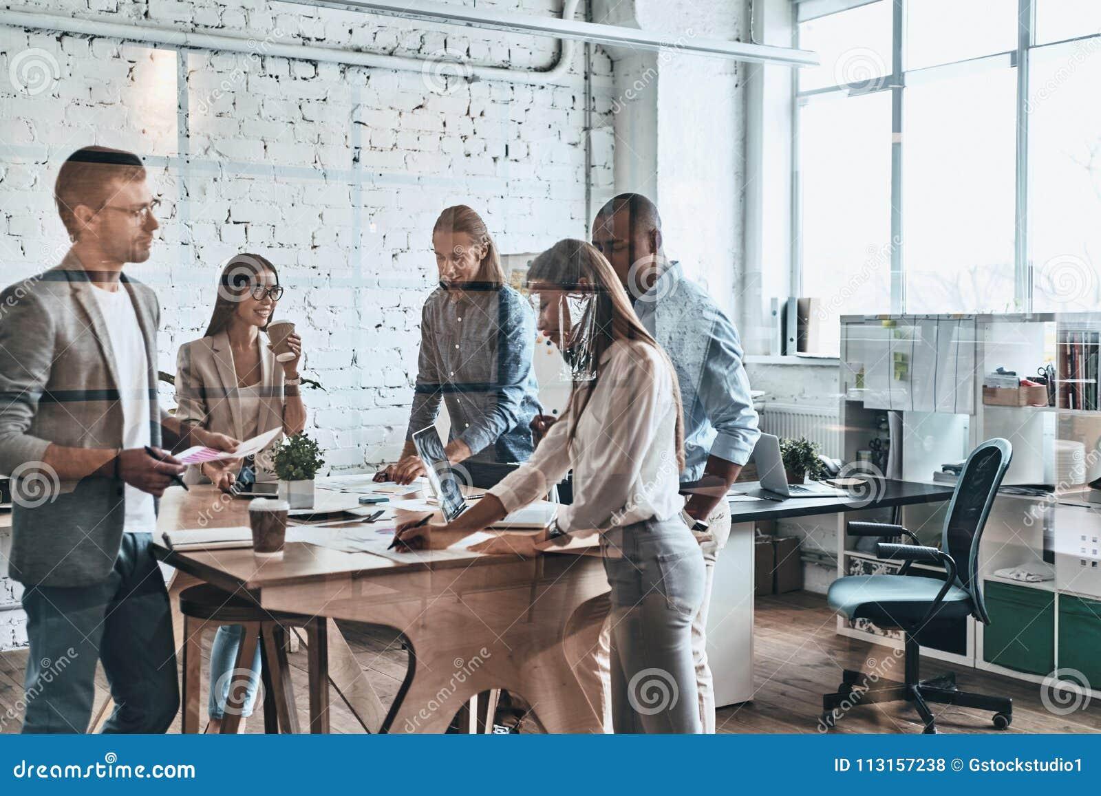 Drużyna przy pracą Grupa młodzi nowożytni ludzie w mądrze przypadkowej odzieży
