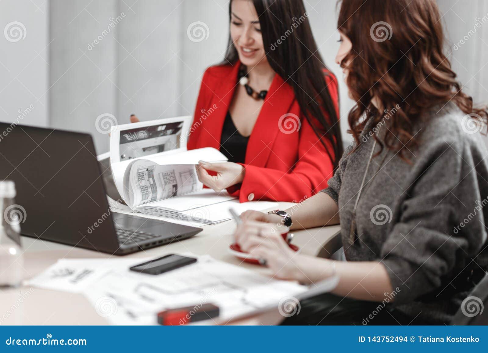 Dru?yna dwa m?odych kobiet projektant pracuje przy projekta projektem wewn?trzny obsiadanie przy biurkiem z laptopem i