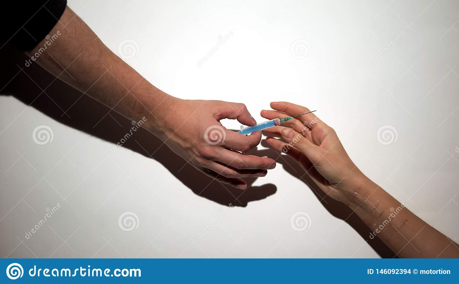Drug dealer hand giving self-inflicted addict syringe with dose, mental disease