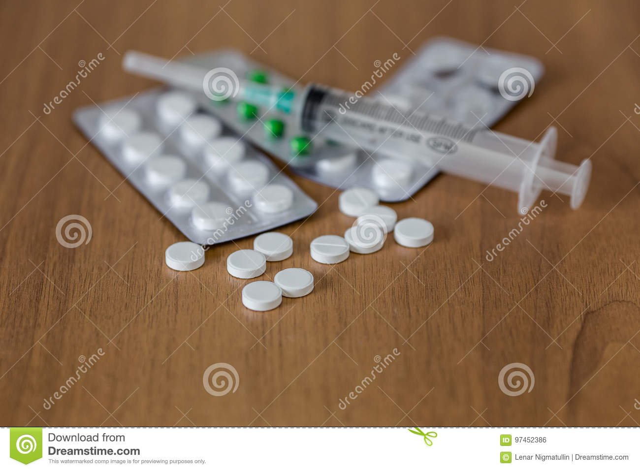 Drugs and syringes on wooden table