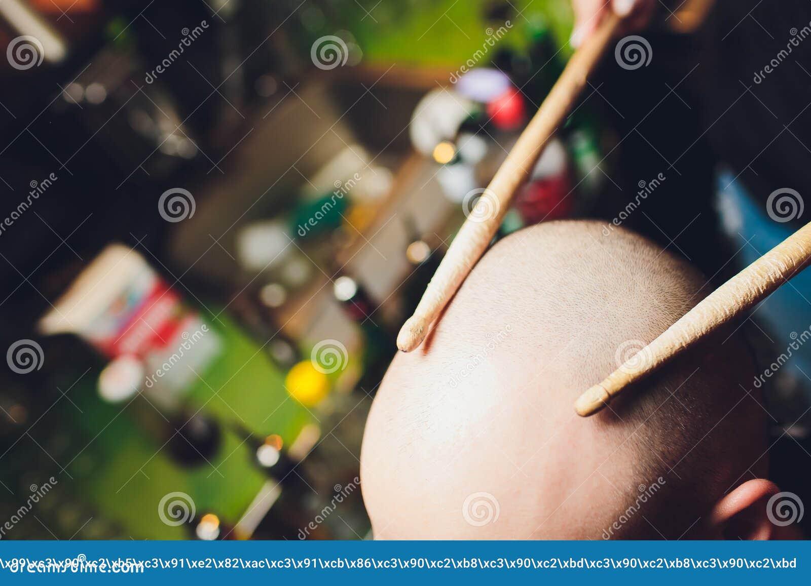 Drum sticks, human head, headache concept, bald.