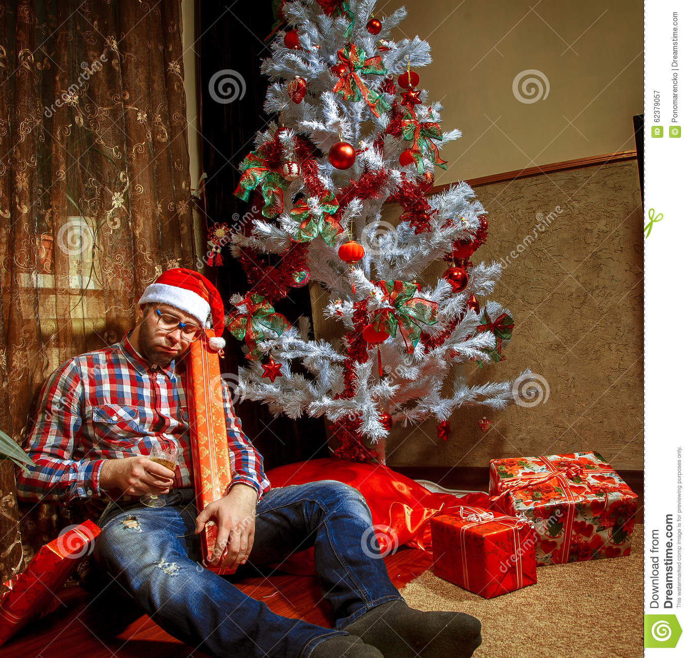 drunk nerd in santa hat lying under the christma tree with a lot - Drunk Christmas