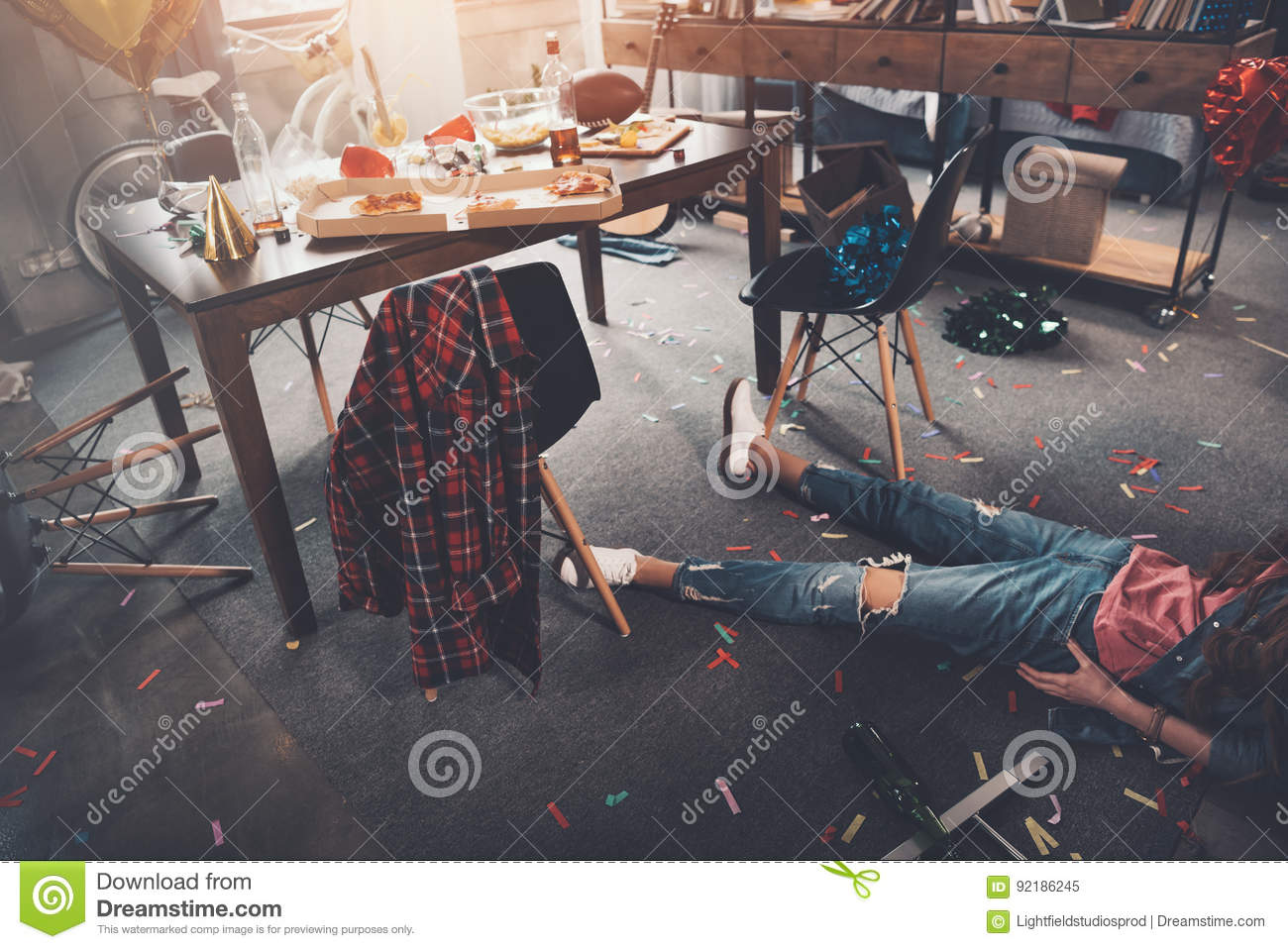 Drunk young woman lying on floor in messy room after party