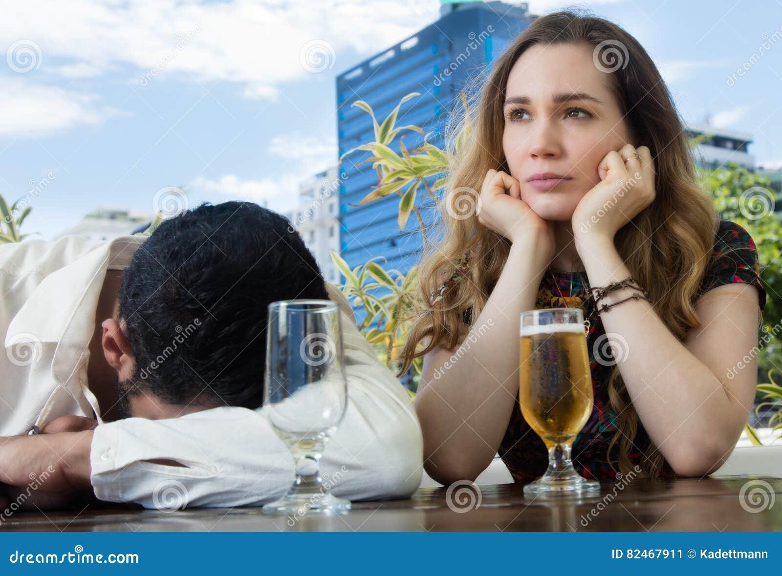 Drunken man with sad girlfriend in a bar