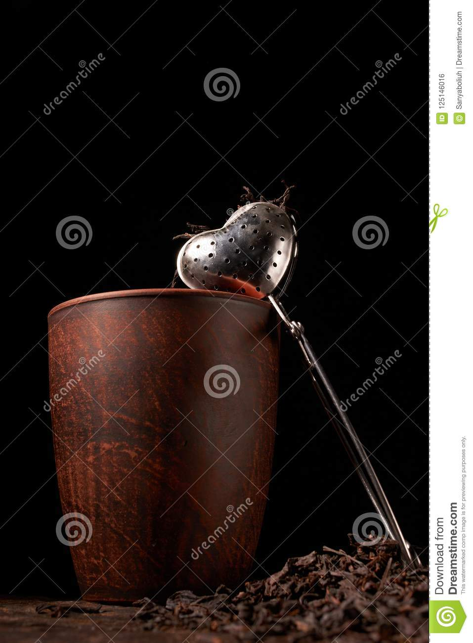dry black chinese tea set,with strainer closeup,cups and teapot on background over old wood board