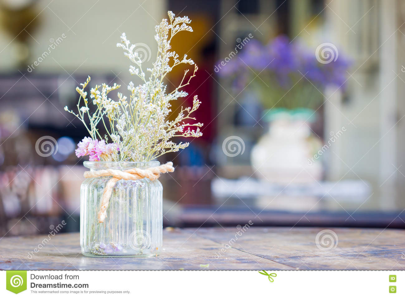 dry flowers in glass vase with rope on blurred background, copyspace