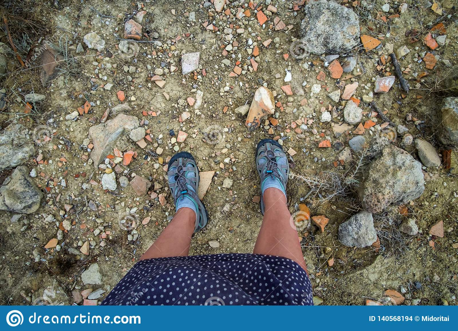 Legs of woman traveller standing on a ground of Cyprus island full of broken ancient pottery shards