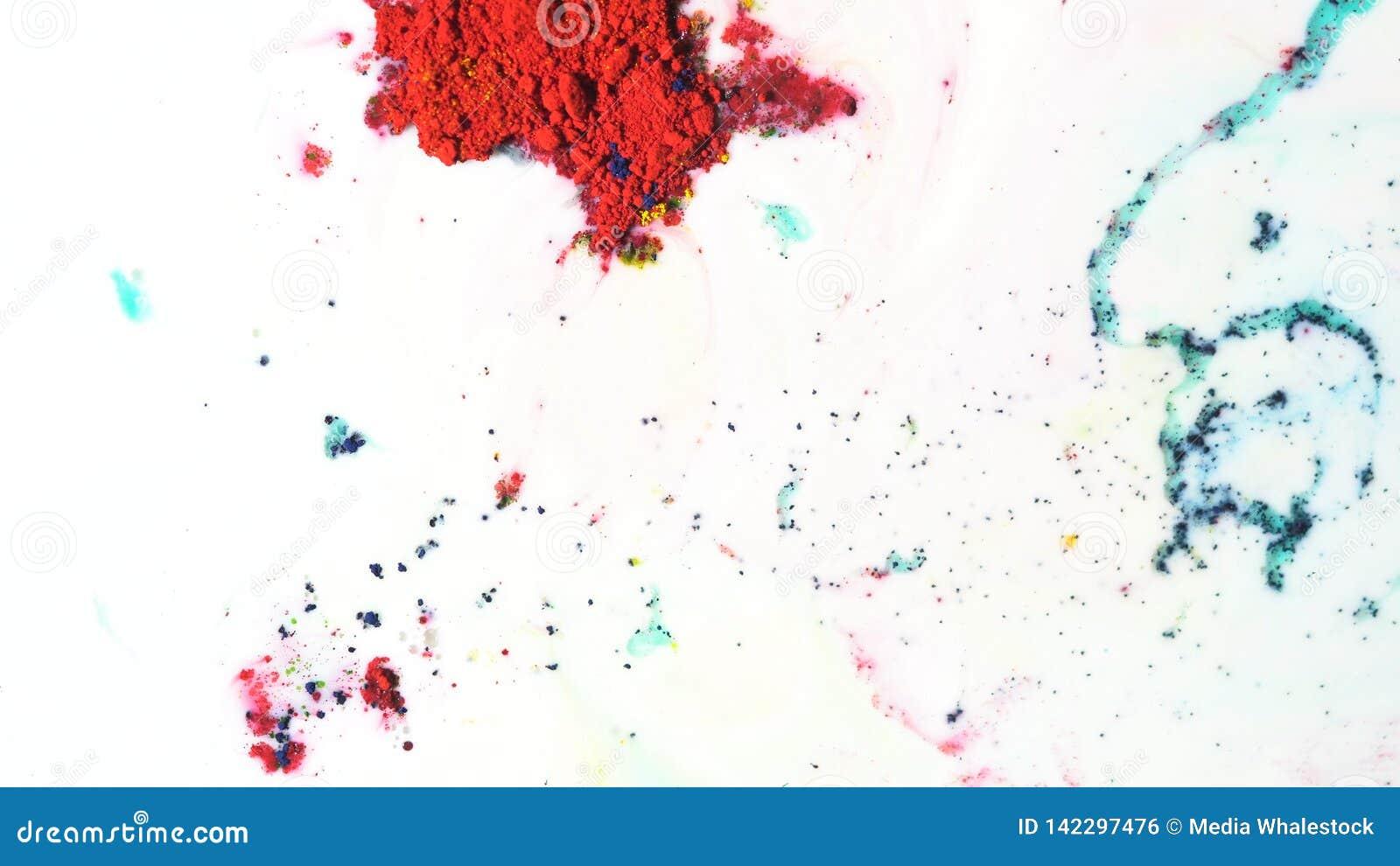 Dry ink colorido que move-se no fundo branco do leite, vista superior Feche acima para a pintura do pó que flutua na superfície d