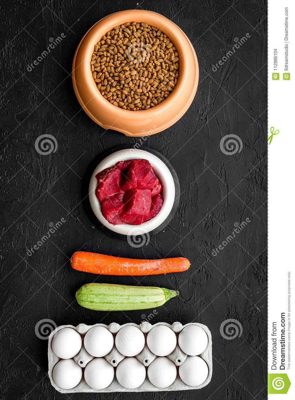 Dry organic pet food with fresh vegetables, eggs and meat in plastic bowl for feeding dogs on black background top view