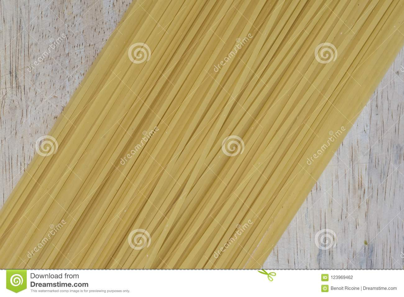 Dry pasta lined up on a board.