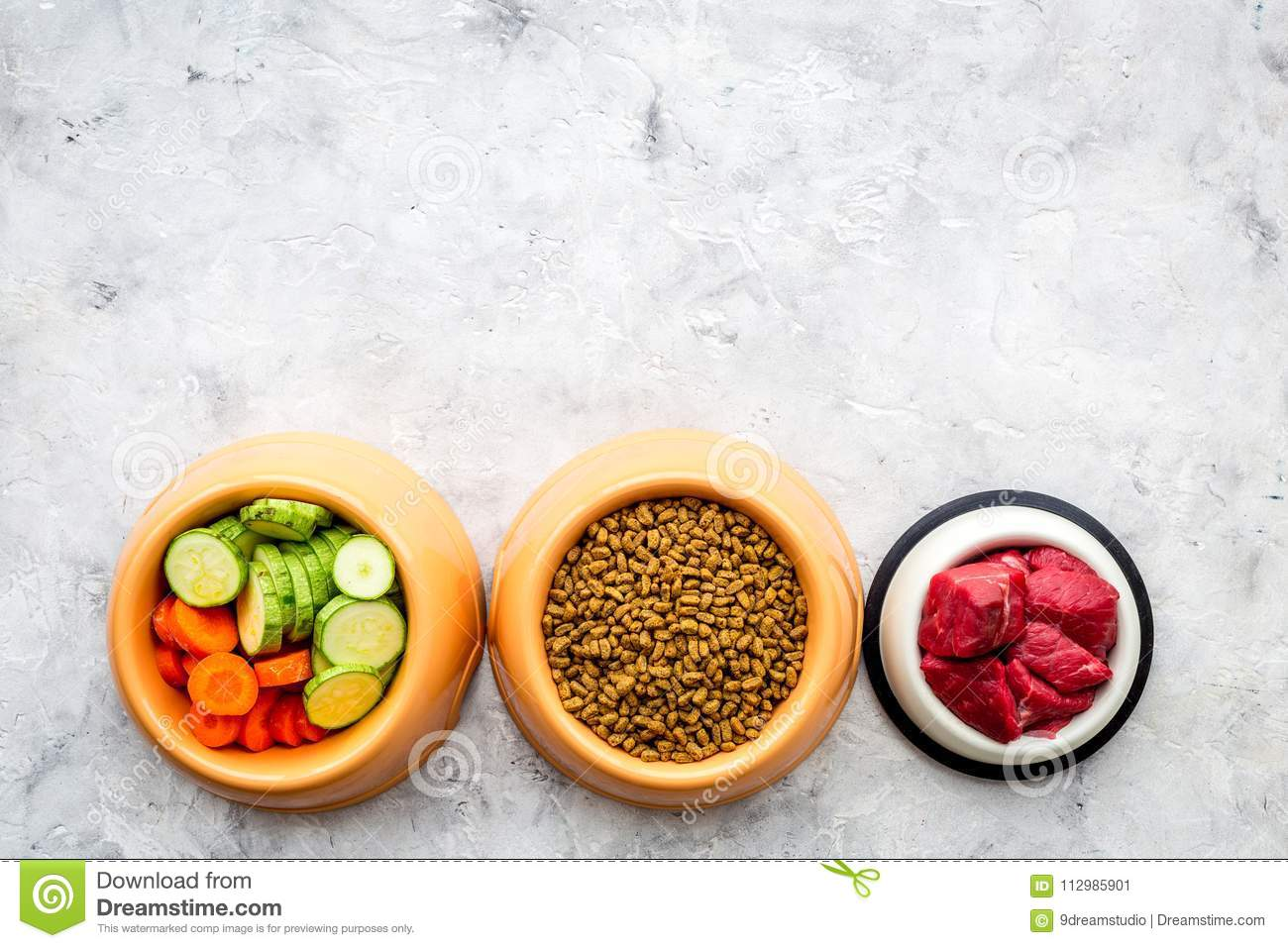 Dry pet food with natural ingredients. Raw meat, cut vegetables zucchini and carrot on stone backgroud top view copy
