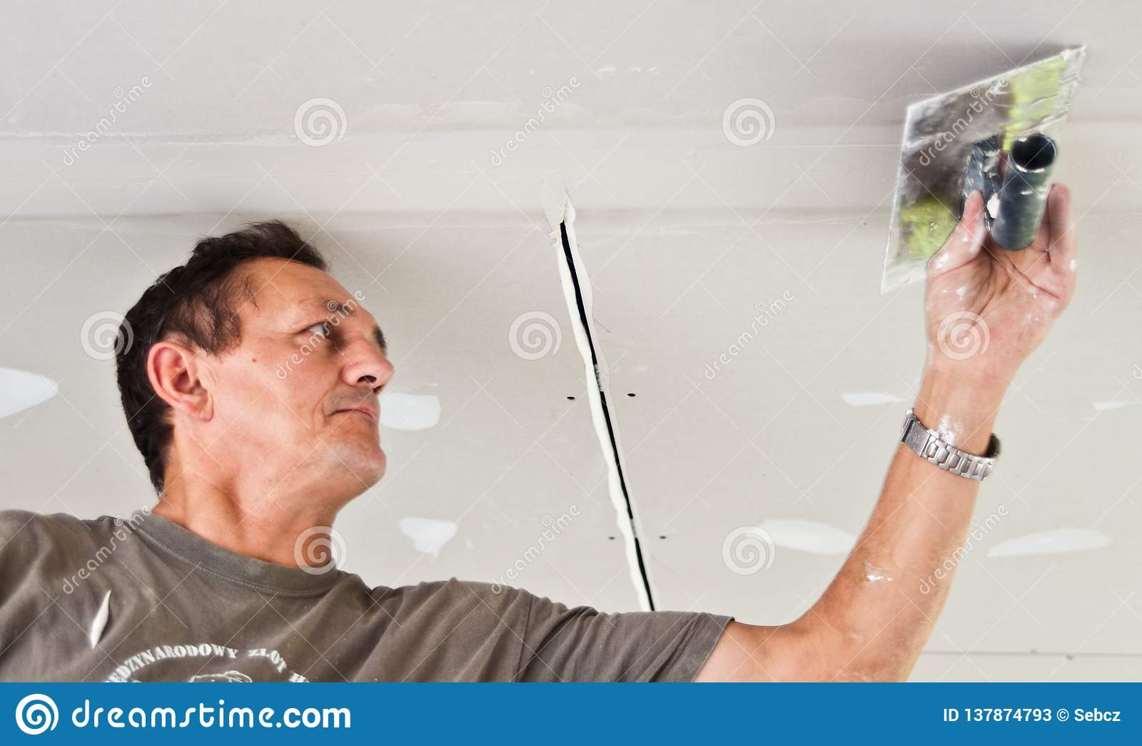 Dry waller working at the ceiling