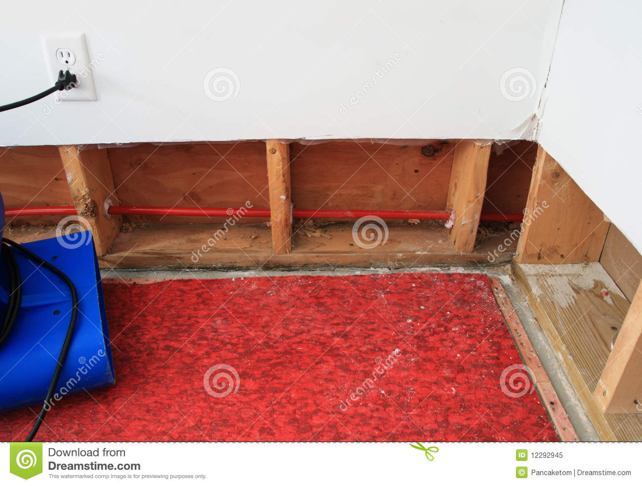 An industrial fan drying water damaged wall and carpet padding in a residential basement