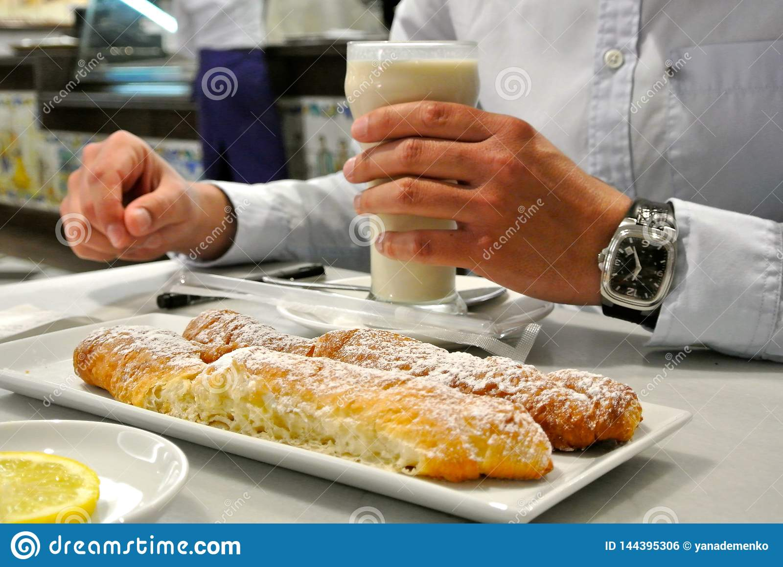 Man is holding glass of traditional Valencian drink, made from yellow nutsedge known as horchata de chufa with farton